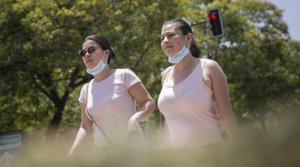 Dos jóvenes pasean con la mascarilla bajada por Sevilla, el pasado23 de junio.