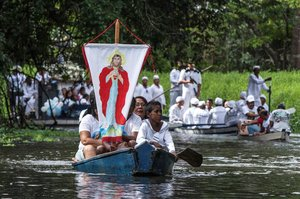 FILE PHOTO Roman Catholic pilgrims display a banner with an image depicting Jesus Christ as they travel in a boat while accompanying the statue of Our Lady of Conception not seen during an annual river procession and pilgrimage along the Caraparu River in Santa Izabel do Para in the Amazon jungle December 8 2012 Picture taken December 8 2012 REUTERS Paulo Santos File Photo