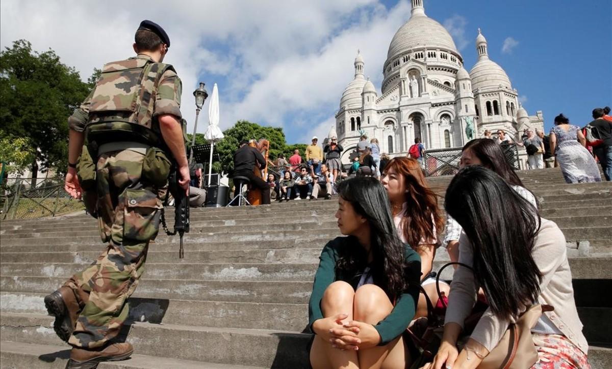 Un soldado francés bajo la mirada de turistas coreanas en Montmartre, enParís.