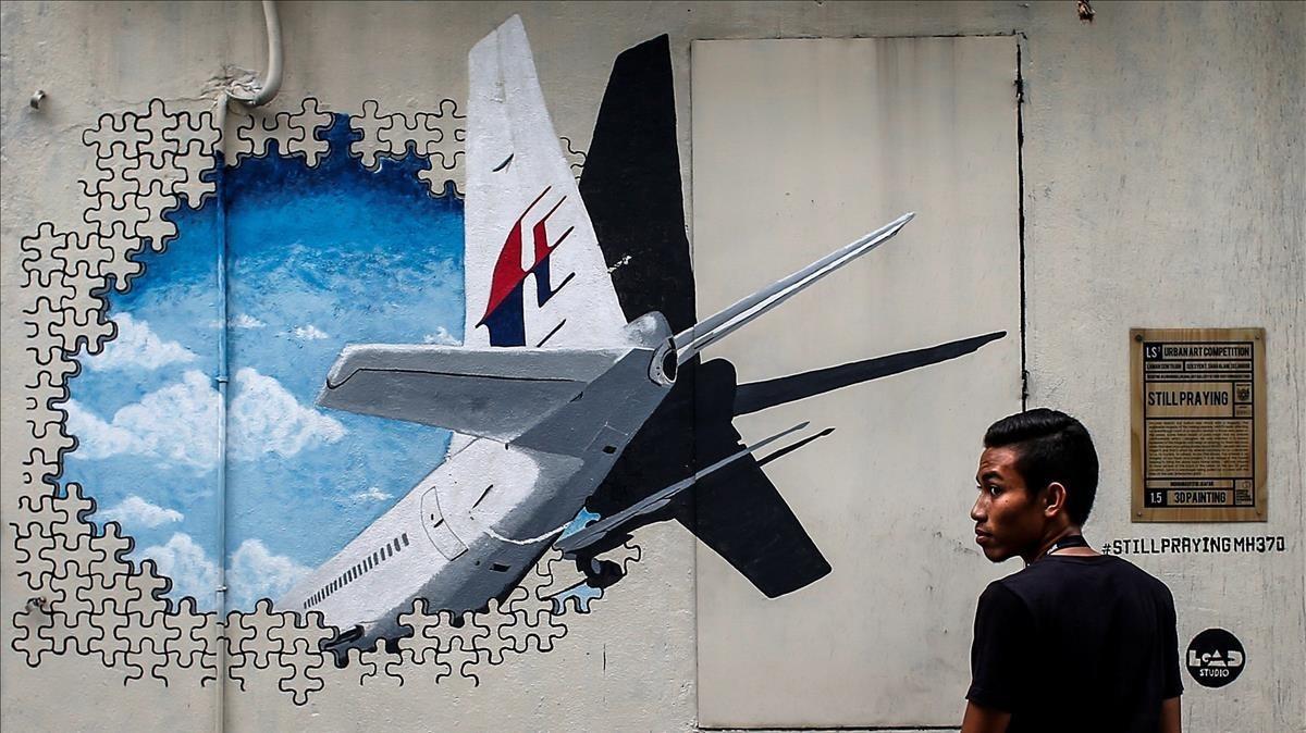 Un joven pasa por delante de un mural del vuelo MH370 de Malaysia Airlines en Kuala Lumpur el 6 de marzo del 2015.