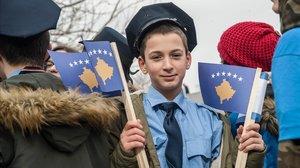 Un joven vestido de agente de policía sostiene una bandera kosovar en una manifestación en Prístina.