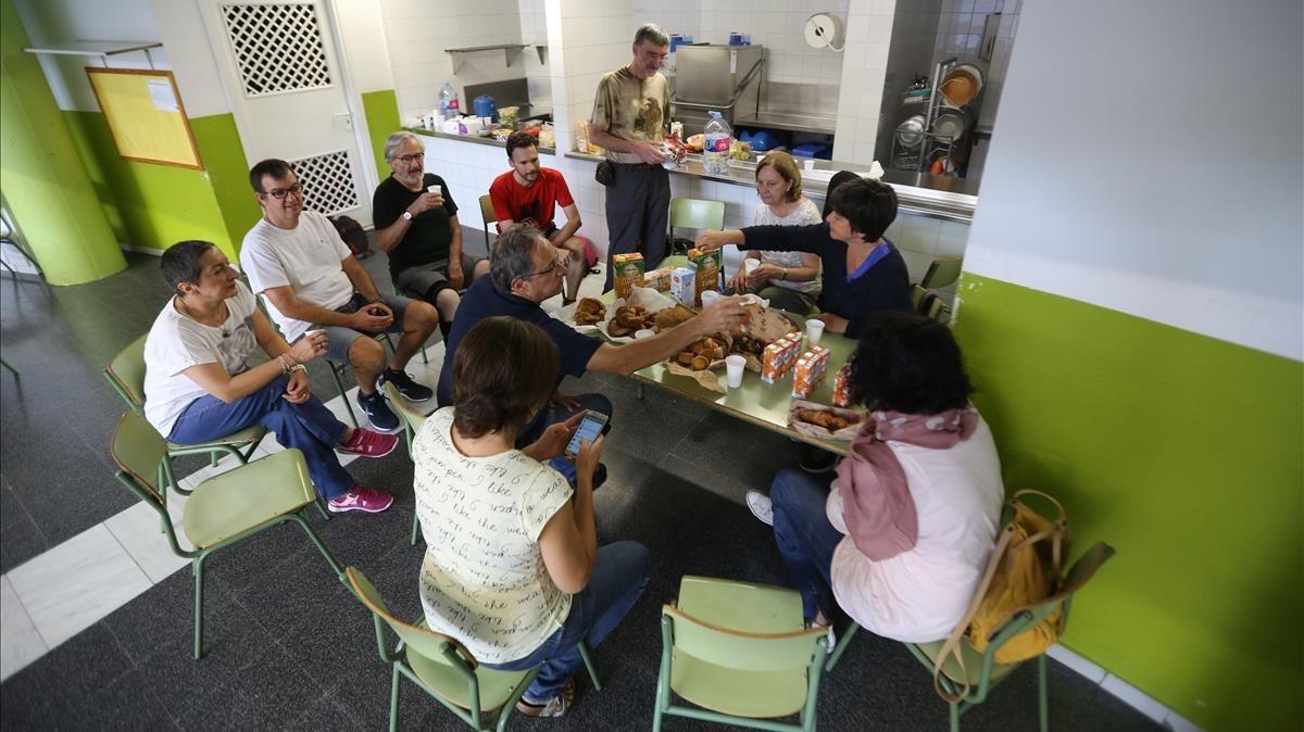 Las personas que han pasado la noche en la escuela Tabor, de Barcelona, desayunando.