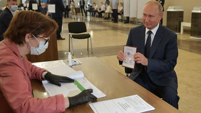 Los rusos votan en una jornada clave del plebiscito constitucional en Rusia. En la foto, Vladimir Putin muestra su pasaporte en una mesa electoral.