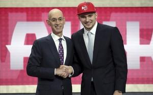 Luka Doncic saluda en el estrado a Adam Silver, comisionado de la NBA, tras su elección