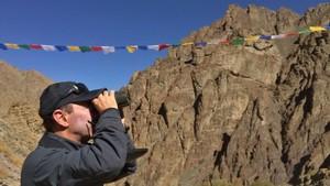 Marc Alonso, con prismáticos, observando un territorio escarpado del parque nacional Hemis, en Ladakh (Cachemira, India).