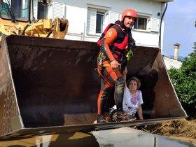 Una mujer es rescatada de su casa en la isla de Euba, este domingo.