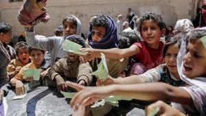 Niños yemenís presentan documentos para recibir las raciones de alimentos proporcionadas por una oenegé local en Saná