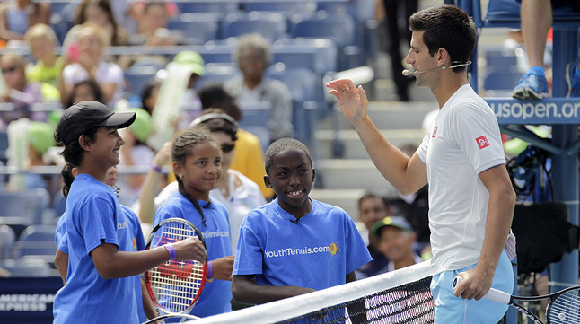 Novak Djokovic saluda a unos niños en la pista Arthur Ashe de Flushing Meadows.