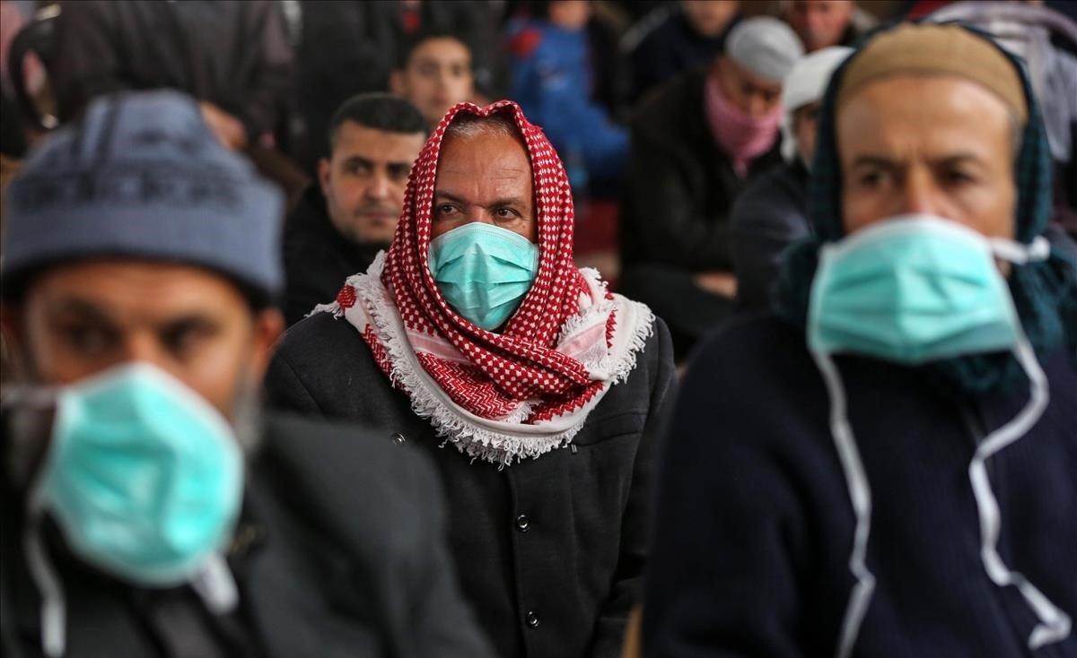 Musulmanes palestinos se protegen con máscaras durante el sermón del viernes, en Khan Youinis, Gaza.