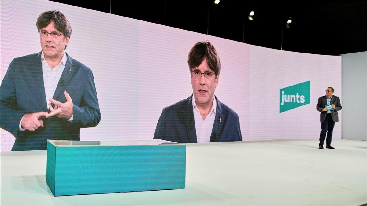 Torra escucha la intervención por videoconferencia de Puigdemont, en el acto inaugural del congreso fundacional del nuevo Junts per Catalunya.