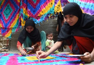 Trabajadoras paquistanís confeccionan alfombras en su casa de Karachi, este lunes.