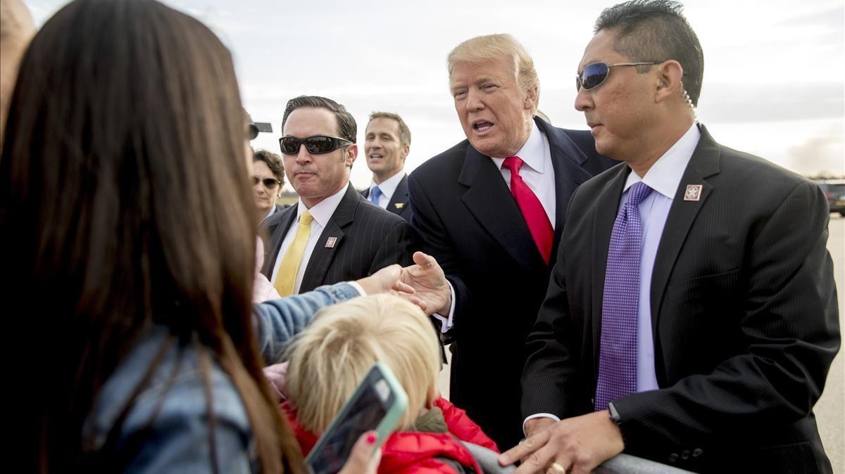 Trump (centro) saluda a varios ciudadanos a su llegada al aeropuerto internacional de Saint Louis, el 29 de noviembre.