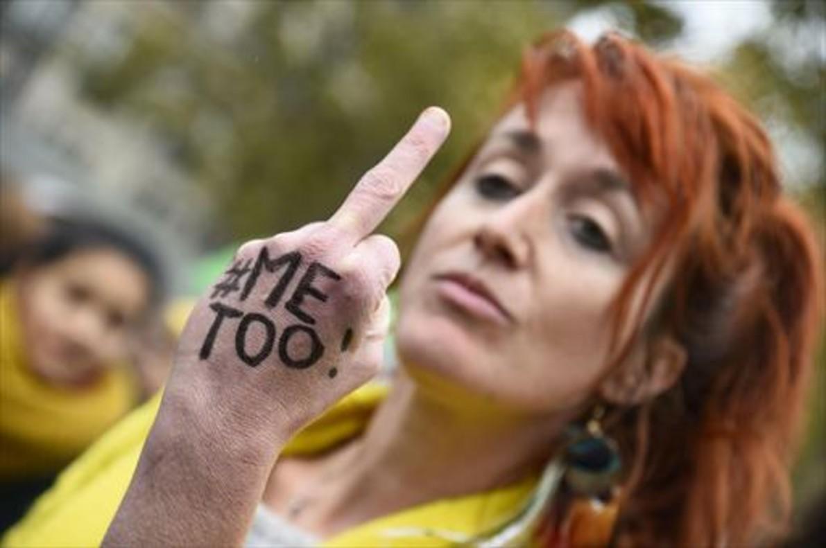 Una mujer con el lema #MeToo escrito en la mano gesticula en París.