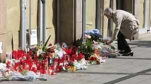 Una mujer deposita flores a las puertas del IES Joan Fuster por el profesor fallecido.