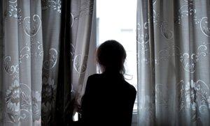 Una mujer observa a través de la ventana de su vivienda, en la que ha permanecido confinada desde que el Gobierno decretó el estado de alarma, en Ourense, el 19 de abril.