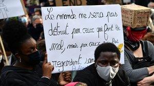 Una mujer sostiene una pancarta en la que se lee: El mundo no será destruido por aquellos que hacen el mal, sino por los que les miran sin hacer nada, este martes en París.