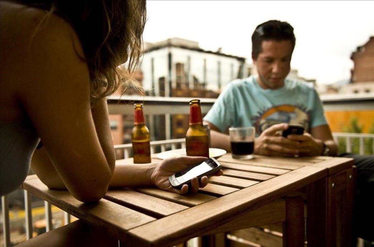 Una pareja de turistas consulta sus móviles en una terraza de Barcelona.