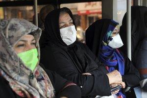 Unas mujeres con mascarilla esperan el autobús, en una parada de Teherán.