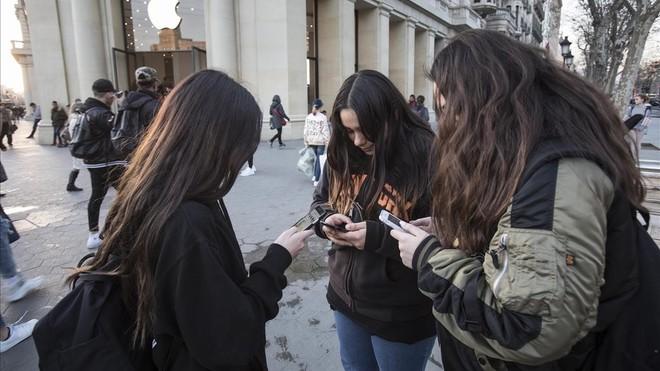 Unos jóvenes manejan sus móviles en el centro de Barcelona