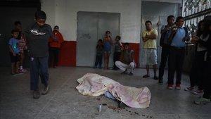 Un grupo de vecinosobservaeste jueves un cuerpo que fue impactado por una bala durante las protestasen Caracas.