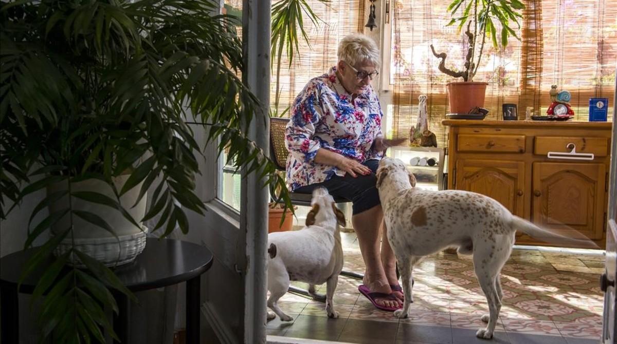 Margarita juguetea con sus perros en la galería de su casa en el Raval.