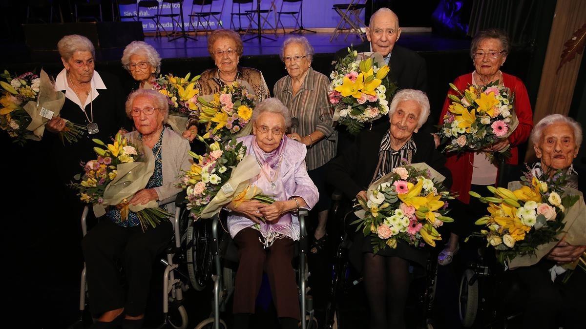 Rafaela Fidelis y Maria Cussó, de pie,cuarta y última por la izquierda, con otras personas centenarias, en el teatro Zorrilla de Badalona, este miércoles.