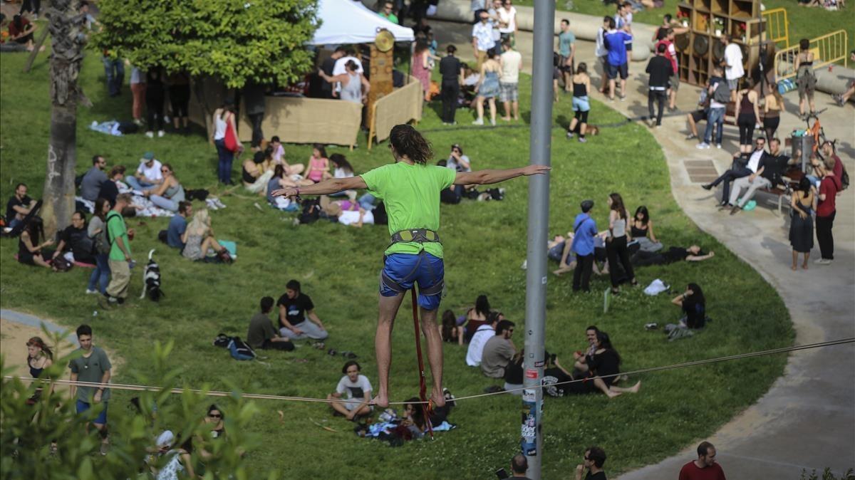 Un joven hace acrobacias sobre una cuerda mientras suena la música, en el parque de Joan Reventós.