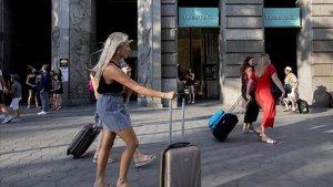 Turistas con sus equipajes pasan por delante de la tienda Tiffanyen el paseo de Gràcia.