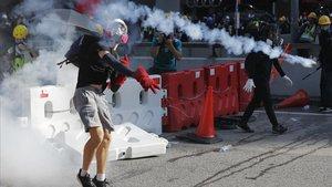 Un manifestante lanza a la policía un bote de gas lacrimógeno.