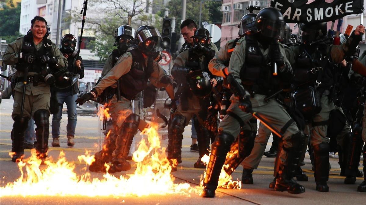 Agentes de policía en Hong Kong se preparan para una actuación entre llamas.