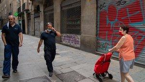 Unas personas pasean por la calle Jaume I en el barri Gòtic.