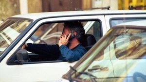 Un hombre habla por teléfono móvil al volante.