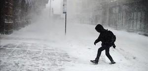 Un neoyorquino intenta avanzar a través de la tormenta de nieve en la ciudad.