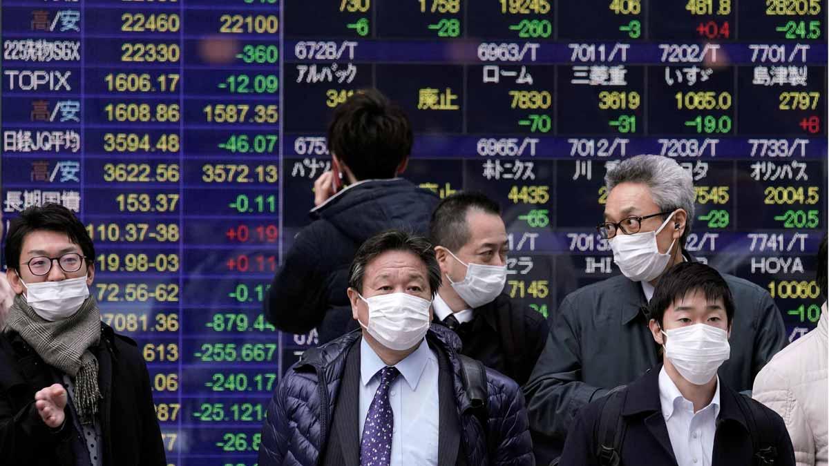 El coronavirus podría costar más de 300.000 millones a la economía mundial. En la foto, ciudadanos protegidos con mascarillas pasan frente a pantallas con información bursatil en Tokio.