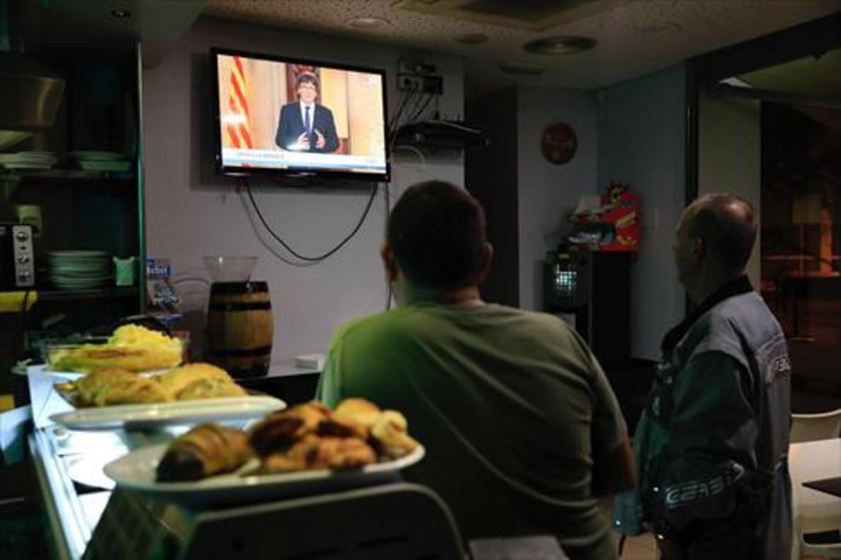 Dos clientes de un bar siguen el discurso de Puigdemont, el miércoles.