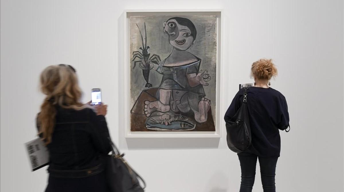 Dos visitantes miran el cuadro de Picasso 'Niño con langosta', en la muestra sobre cocina del pintor malagueño, en el Museu Picasso.