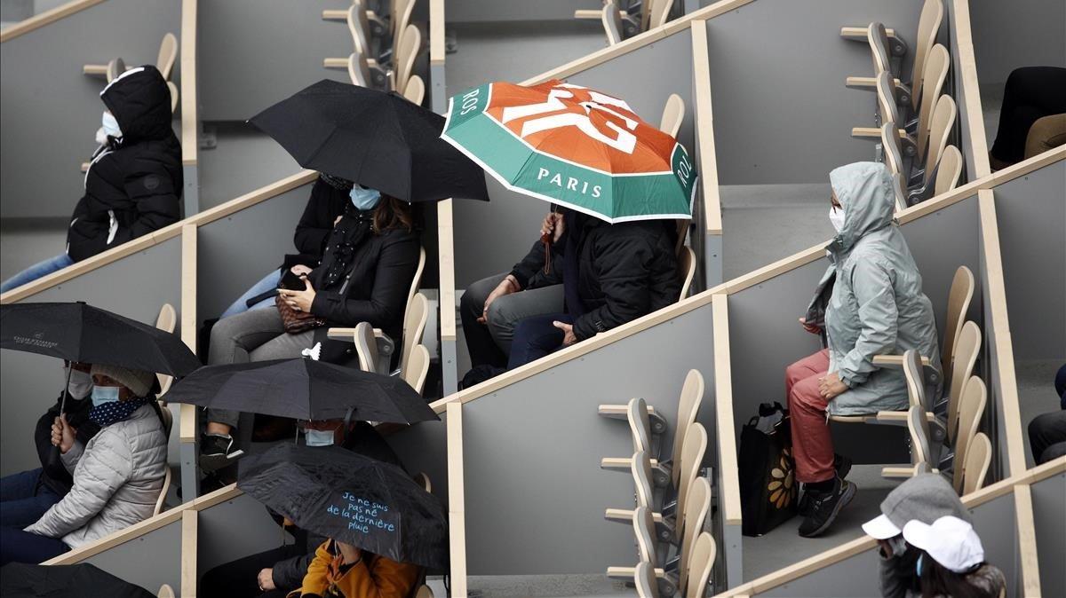 Espectadores en Roland Garros observando un partido de tenis femenino.