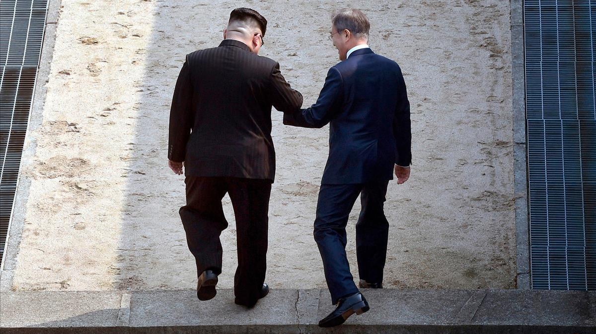 El líder norcoreano, Kim Jong-un (izquierda), y el presidente surcoreano,Moon Jae-in, se dan la mano para cruzar la línea de demarcación entre los dos estados en la zona desmilitarizada de Panmunjon, el 27 de abril del 2018.