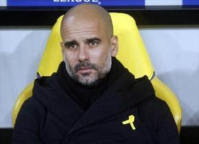 Guardiola, en el banquillo del Manchester City con el lazo amarillo.