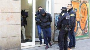 Imagen del momento en el que la policía sale de uno de los pisos con un detenido por tráfico de droga