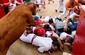 Un grupo de mozos grabando cómo les pasa una vaquilla por encima.