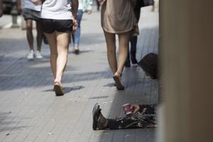 Un indigente pide limosna en una calle de Barcelona.