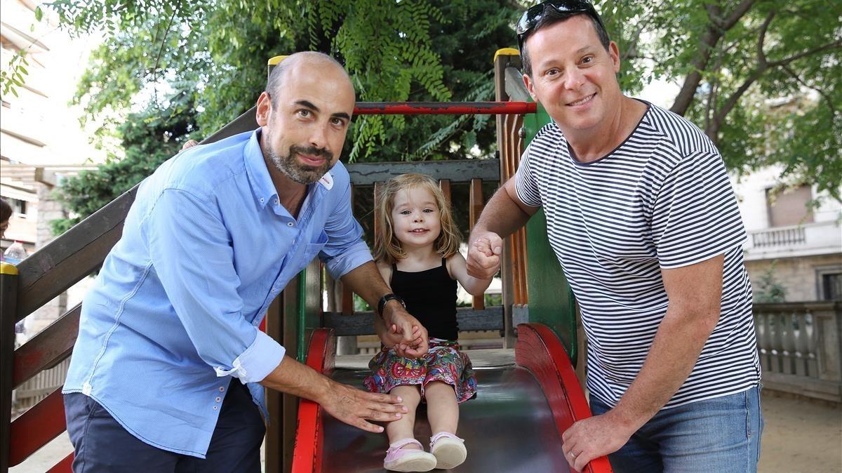 Jordi Salinas y Josep Vidal columpian a su hija Marina, en el 2014.