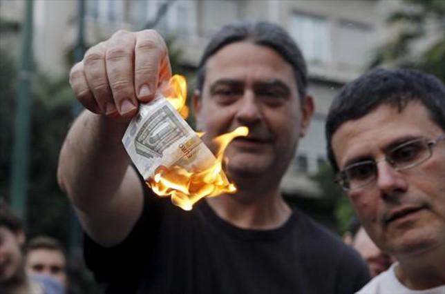 Un manifestante anti-austeridad quema cinco euros en Atenas.