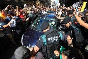 Mossos ayudan a guardias civiles a salir de una concentración de protesta ante la Conselleria d'Afers Exteriors.