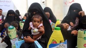 Mujeres yemenís sostienen a sus hijos mientras esperan el reparto de comida en la ciudad de Al Hudayda, en la costa oeste del país.