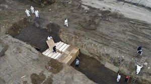 Operarios entierran en una fosa común a varios fallecidos por el coronavirus, en la isla de Hart (Nueva York).