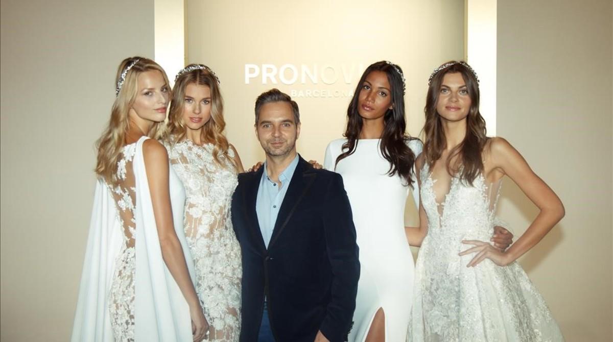 Hervé Moreau, diseñador de Pronovias, posa con algunas modelos tras el desfile de la colección Atelier 2017, en Nueva York.