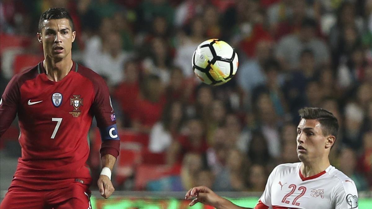 Cristiano Ronaldo y el suizo Schar pugnan por un balón en Lisboa.