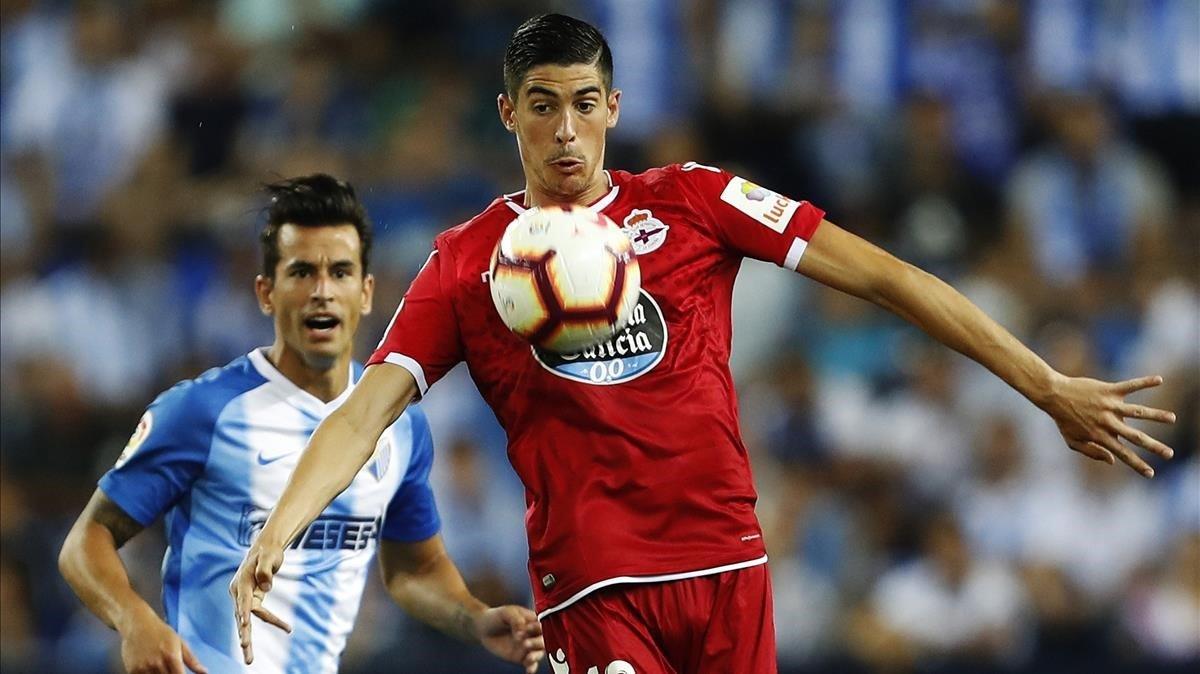 Carlos Fernández, del Depor, controla el balón presionado por Luis Hernández, del Málaga.